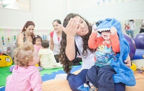 Sala de creche. Duas professoras estão sentadas ao fundo ao lado de duas crianças. Elas estão interagindo entre si. À frente, uma professora está sentada no chão com um bebê no colo, que veste um capus azul com dentes e olhos. Uma outra bebê observa os do