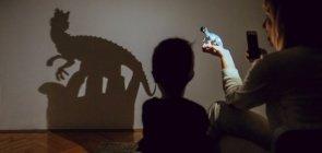 Foto de um teatro de sombras, com uma mulher segurando um dinossauro com uma mão e a lanterna do celular com a outra, criando o efeito de um dinossauro grande na parede. Ao seu lado, tem uma criança