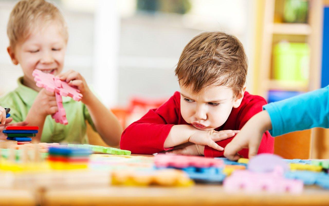 Alunos brincam em sala de aula com brinquedos coloridos em volta de um aluno com cara de bravo