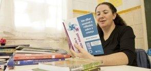 A professora Mara Mansani está sentada numa mesa de sala de aula e lê um livro chamado