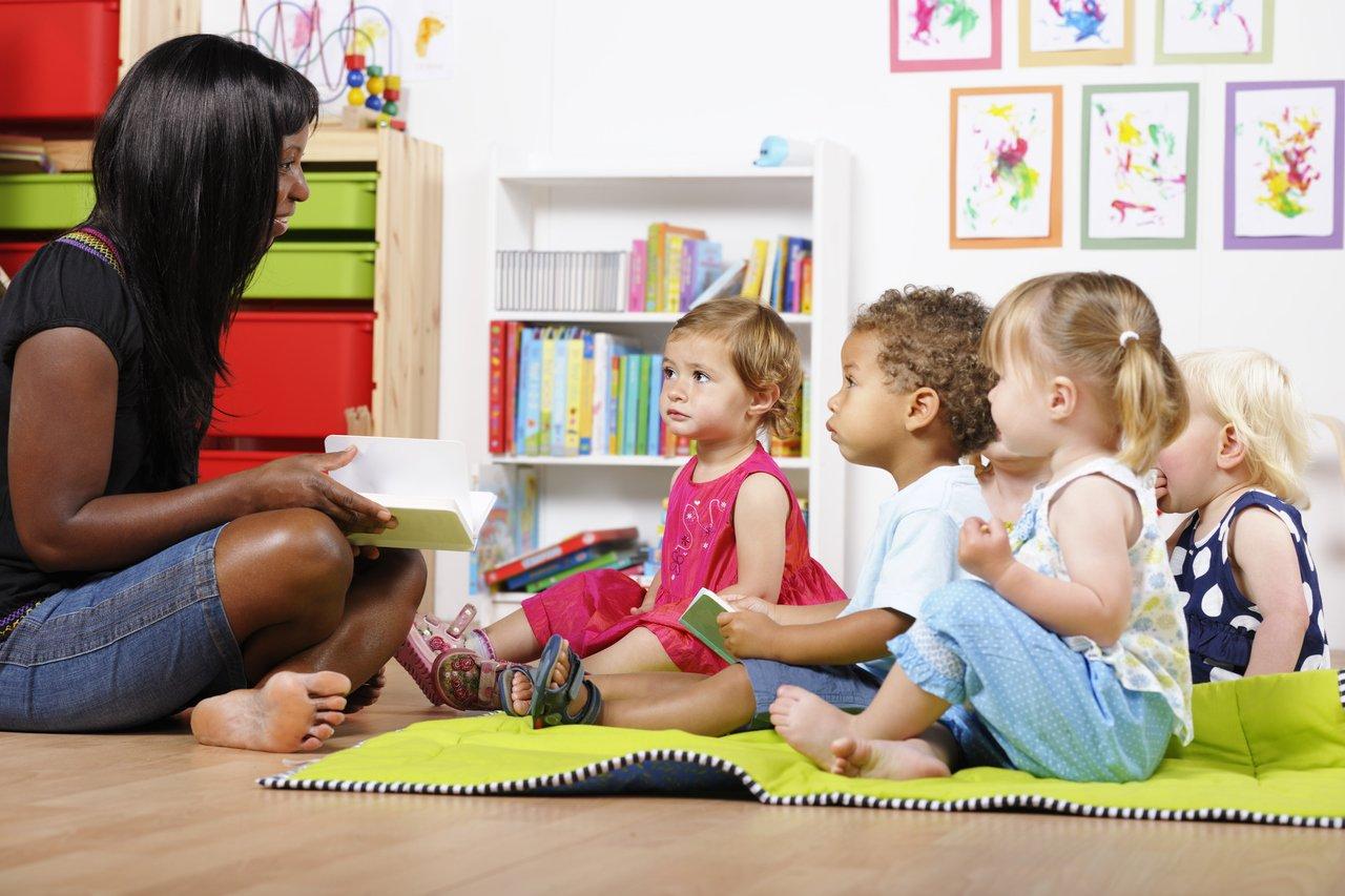 Professora sentada no chão lê um livro para crianças pequenas em uma sala de aula da Educação Infantil
