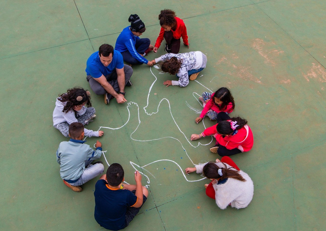 O professor Luiz Gustavo Bonatto Rufino e seus alunos conversam sentados no chão da quadra sobre os contornos dos corpos desenhados com giz