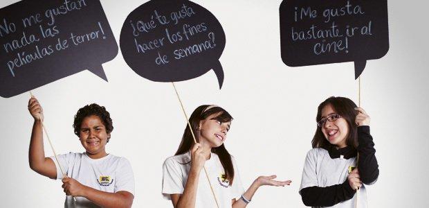 Alunos seguram placas com frases sobre o verbo gustar nas aulas de espanhol. Foto: Patricia Stavis