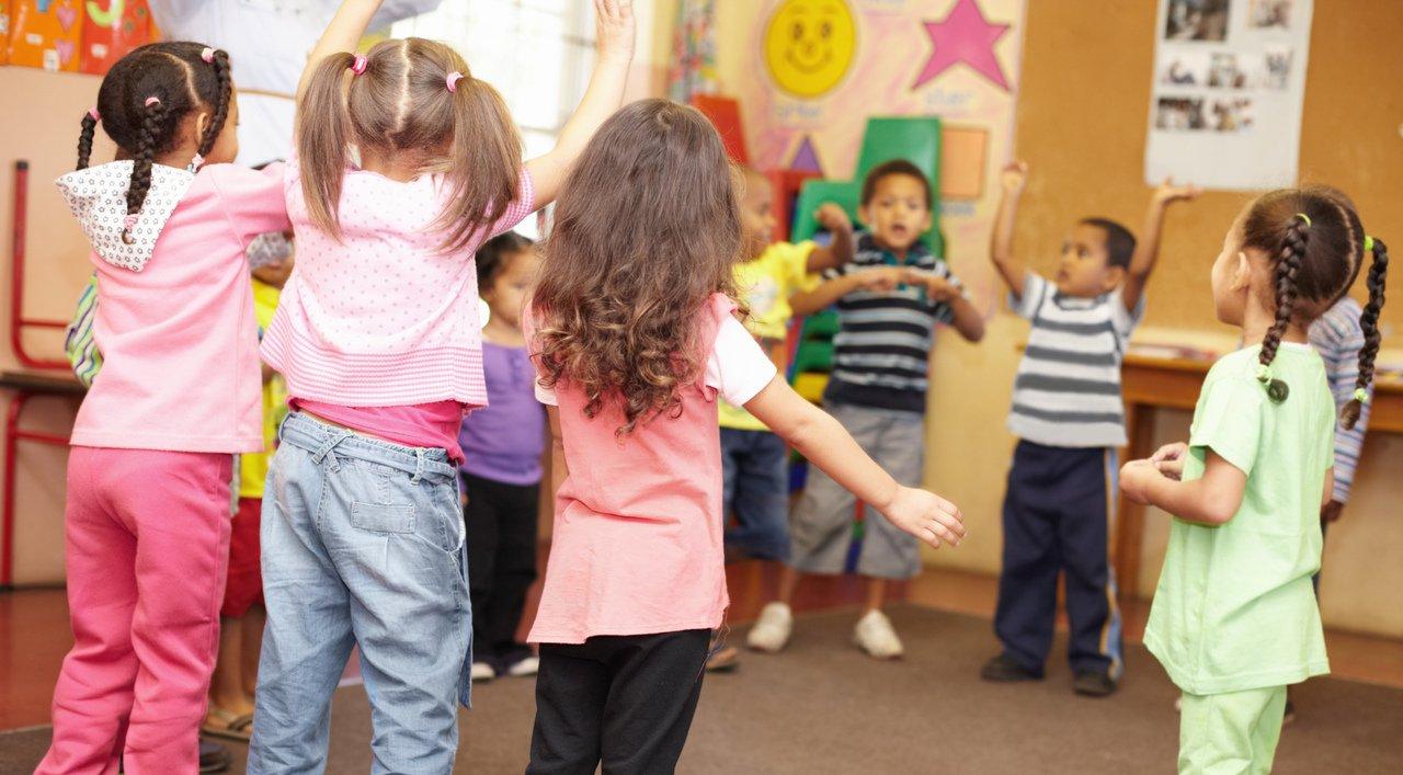 Crianças reunidas em uma roda dançam e cantam em sala de aula