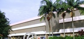 Um prédio horizontalmente grande com 4 coqueiros na frente e uma escultura circular