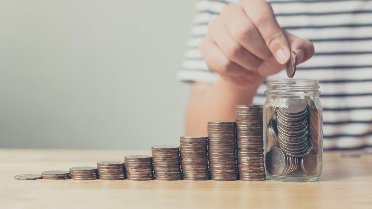 Pilhas de moedas formando uma escada crescente até um pote de vidro cheio de moedas com a mão de uma mulher colocando uma última moeda no pote