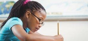 Menina escreve a lápis no caderno ao fazer lição