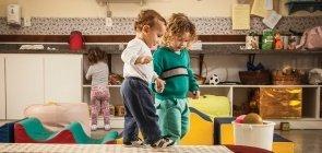 Duas crianças em creche caminham sobre tábua no chão
