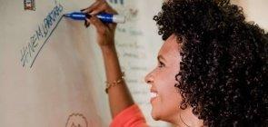 Uma mulher sorrindo escreve em um quadro branco