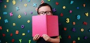 Um menino de origem oriental de cerca de cinco anos com óculos e segurando um livro aberto perto do rosto. Ao fundo, há várias letras e números de alfabeto móvel de plástico