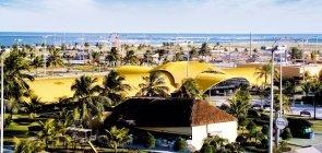 Na foto, vê-se a Orla de Atalaia, com uma faixa verde beirando a praia com algumas construções e coqueiros
