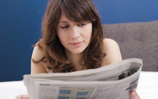 Moça de cabelo comprido e franja lê jornal debruços
