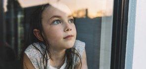 Menina branca, com olhos azuis e cabelo longo e castanho olha pela janela