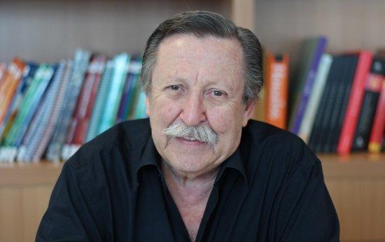 Imagem de um homem idoso de bigode com uma estante de livros ao fundo