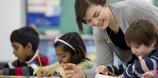 Uma professora de cabelos presos curvada na mesa de um estudante