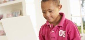 menino com sindrome de down utilizando um notebook