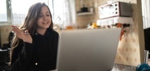 Foto de menina na cozinha conversando na frente do computador