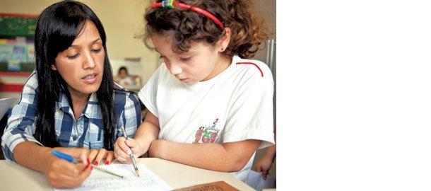 A professora Eudes auxilia os estudantes já alfabetizados a escrever. Foto: Fernanda Preto