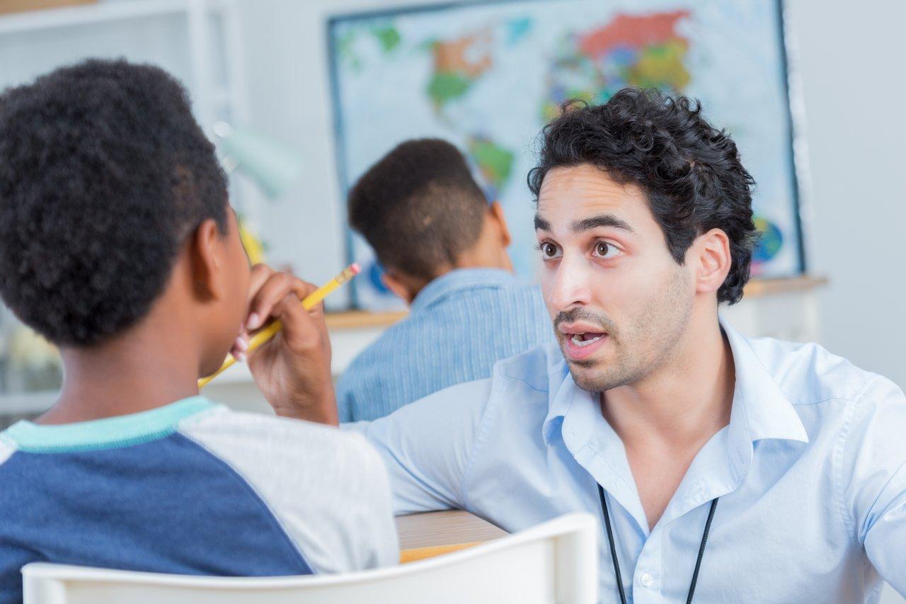 Professor de frente para a câmera parece discutir com aluno sentado em carteira, de costas para a câmera, em uma sala de aula