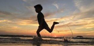Menino corre na praia no entardecer no Rio de Janeiro