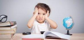Criança com cara de triste apoiada em mesa de estudo