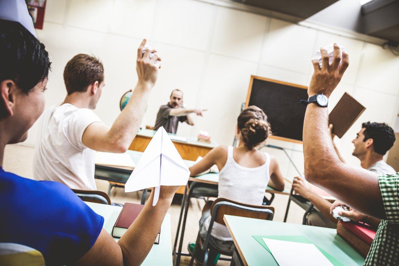 Alunos atiram papéis, cadernos e aviões de papel contra professor sentado em sua mesa na frente da sala