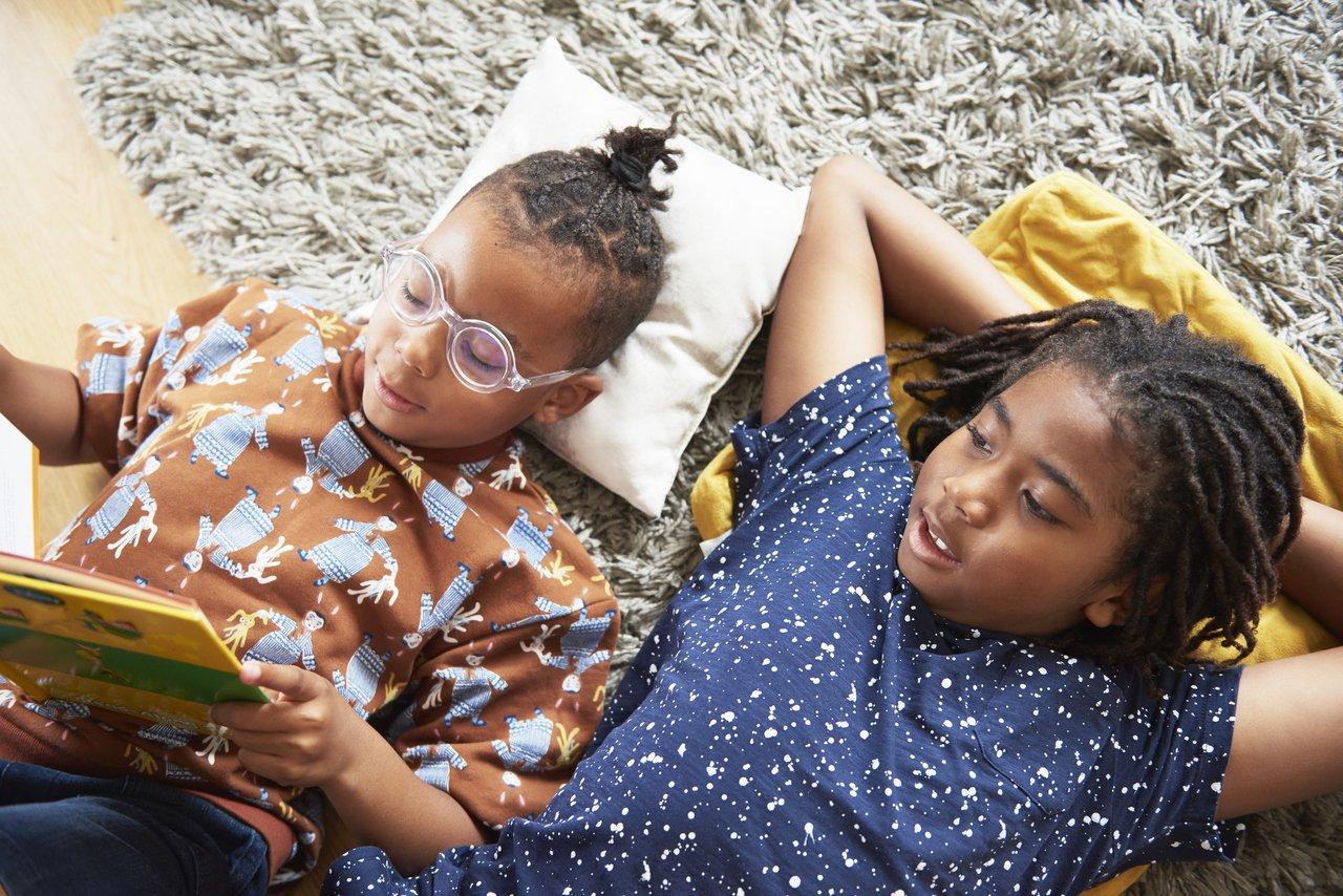 duas irmãs deitadas no chão lendo um livro