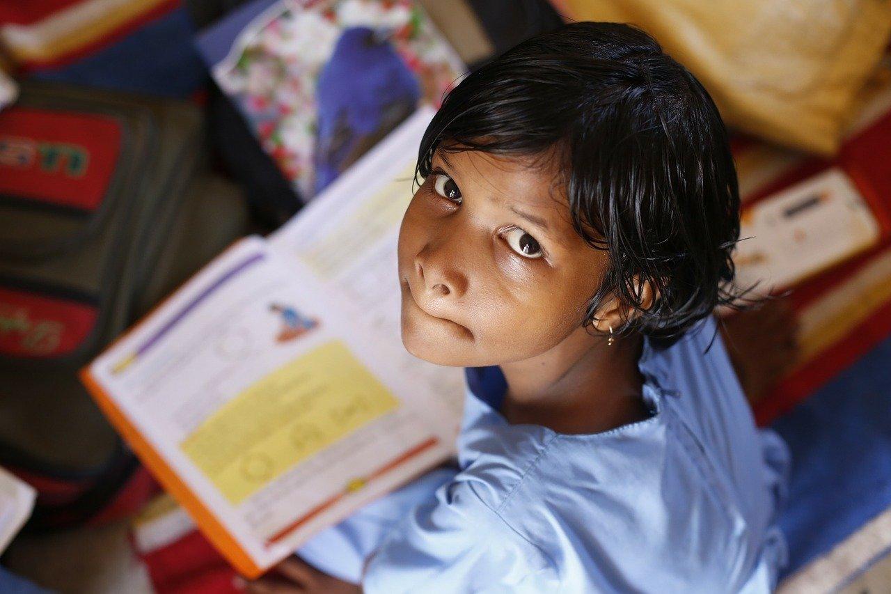 Garota de pele escura e cabelo liso sentada no chão olhando para cima com livro aberto no colo