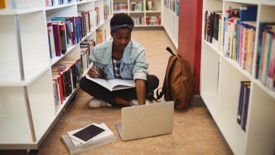Menina negra sentada no corredor de uma biblioteca estudando com um caderno no colo e um computador