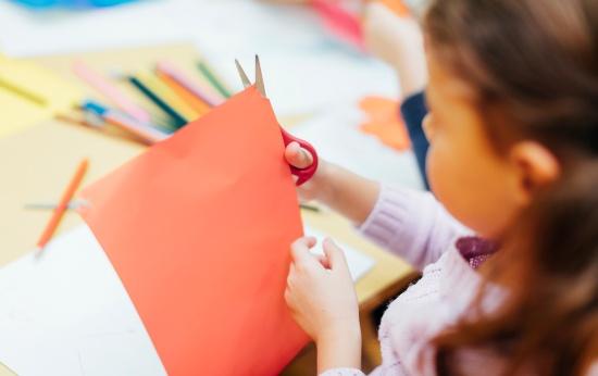 Criança brincando com papel e tesoura