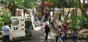 Vários quadros e obras de arte estão expostos em uma praça da cidade de Embu das Artes, em São Paulo. Pessoas passam pelo lugar, algumas olham as telas.
