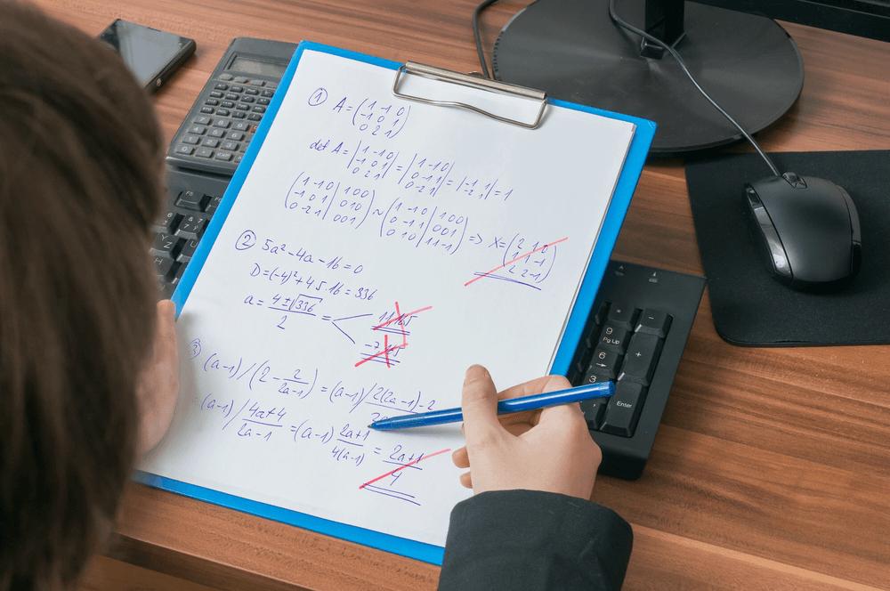 Pessoa corrigindo uma folha de atividades com caneta vermelha e fazendo X nas contas erradas. A folha está presa em uma prancheta.