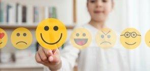 Uma menina de cerca de 7 anos desfocada aponta para uma carinha feliz em uma lista de emoticons à sua frente