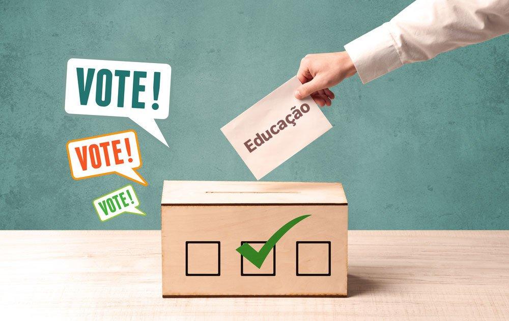 """Caixa de madeira com uma abertura superior onde um braço de um homem de camisa longa bege deposita um papel escrito """"educação"""". Ao lado da caixa, três balões trazem escrito a palavra """"vote"""""""