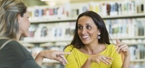 Professoras conversam na biblioteca em clima amistoso
