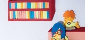 Ilustração. À direita há tres fileiras em cada uma um aluno segurando um livro. No fundo da sala há uma estante cheia de livros