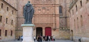 Uma estátua em primeiro plano e, ao fundo, um grupo de pessoas está no pátio da Universidade de Salamanca, na Espanha.