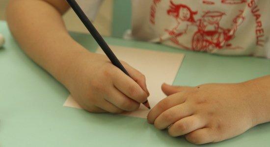 Criança escreve numa folha de papel em branco