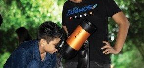Criança olha por um telescópio, ao lado, um homem vestindo a camiseta escrito projeto cosmos observa o menino