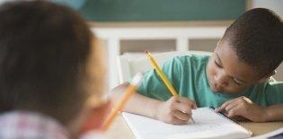 um menino negro de cerca de 6 anos está debruçado sobre a carteira escrevendo