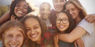 Adolescentes de várias etnias abraçados, diversidade