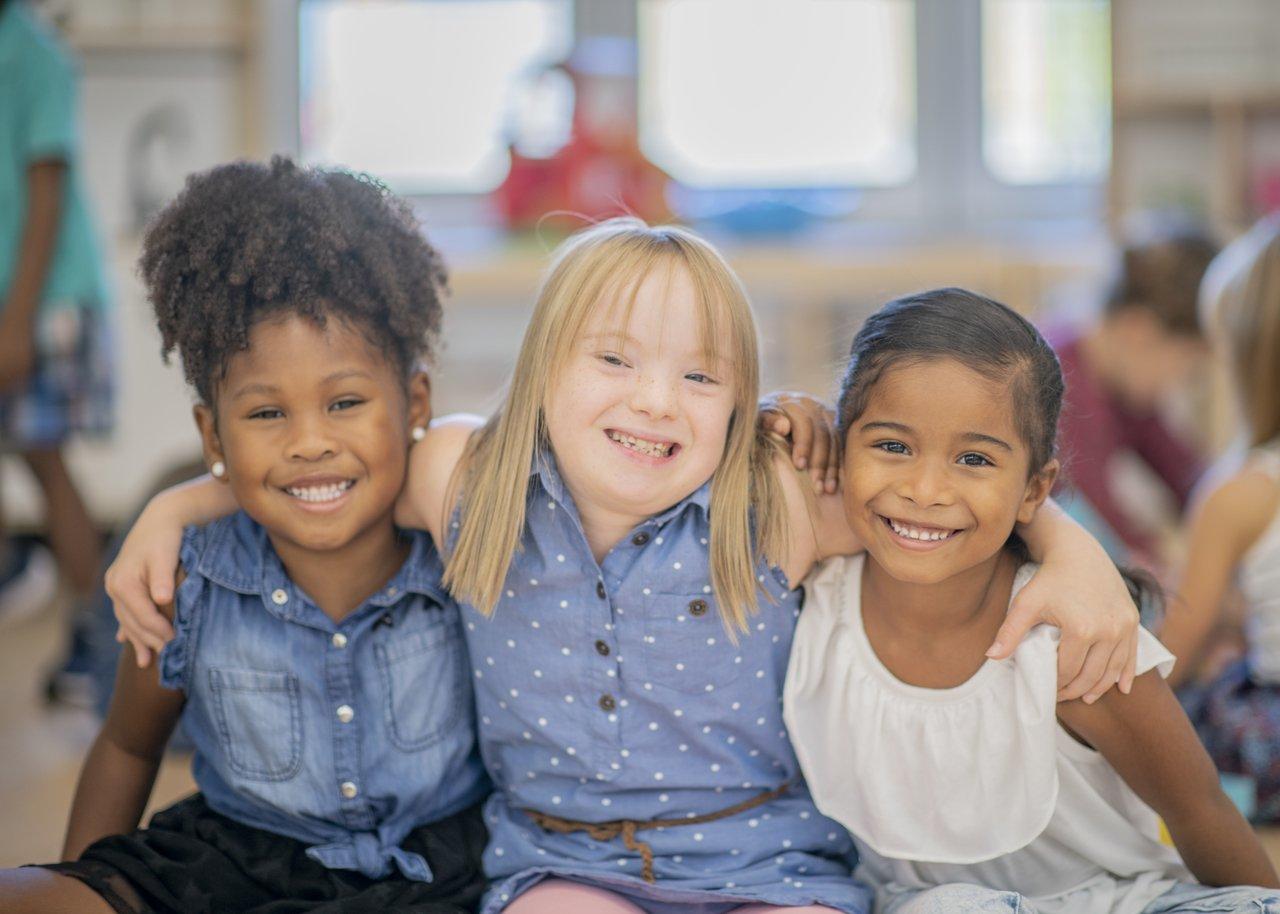 Três alunas, uma de inclusão ao centro, se abraçam e olham para a câmera sorrindo em uma sala de aula