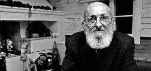 Foto em branco e preto, homem careca com barba branca, usa óculos e está sentado com braços cruzados