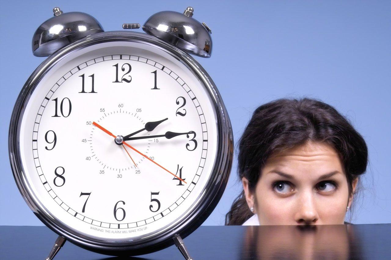 Mulher atrás de uma mesa olha ansiosamente para um relógio em primeiro plano