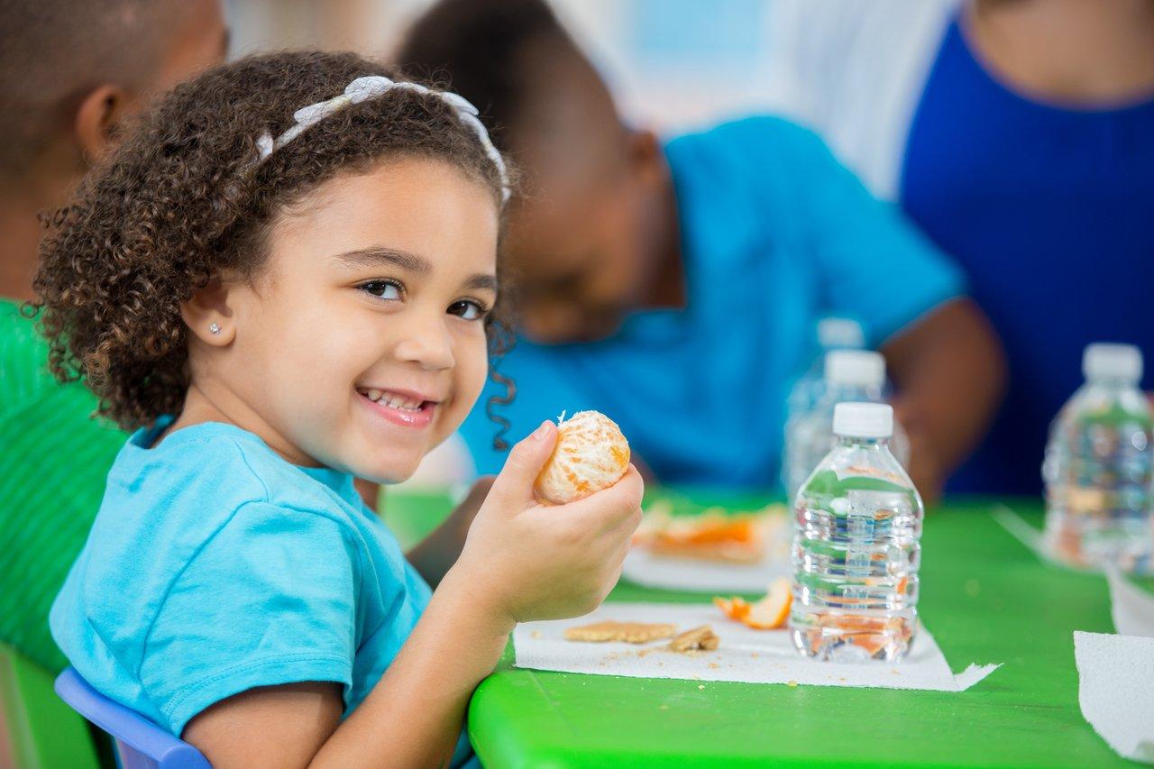Menina sentada em uma sala de aula olha para a câmera e sorri enquanto segura uma tangerina descascada