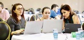 três professoras, cada uma com seu laptop, sentadas ao lado uma da outra diante de uma mesa azul (onde os computadores estão abertos)
