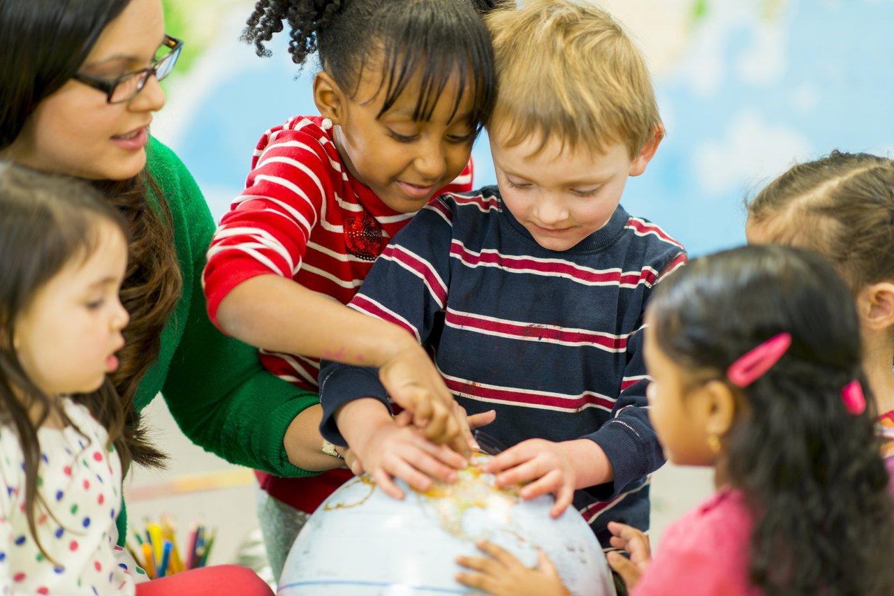 Crianças apontam para um globo terrestre, cercada por outras crianças e observadas pela professora