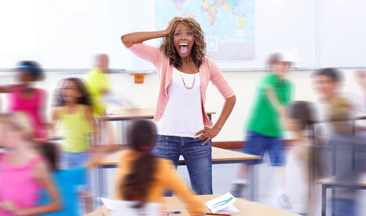 Professora angustiada em meio a sala de aula com alunos correndo e fazendo barulho
