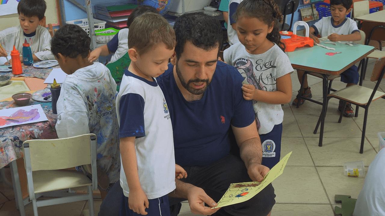 Professor Evandro Tortora conversa ajoelhado com um aluno, que mostra seu desenho