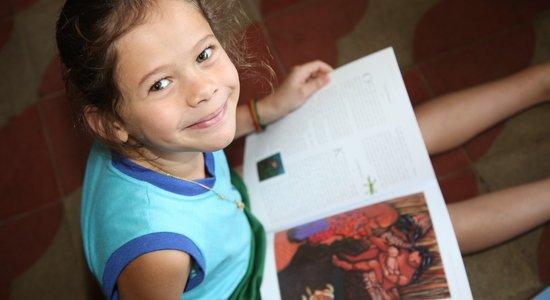 Menina lê um livro em sala de aula (Foto: Manuela Novais)